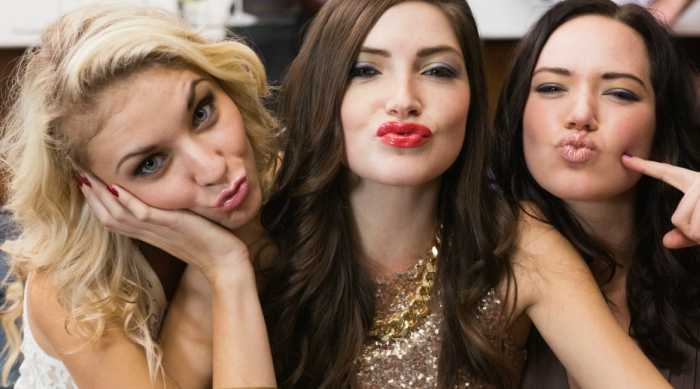 Three girls taking a picture and making a duck face