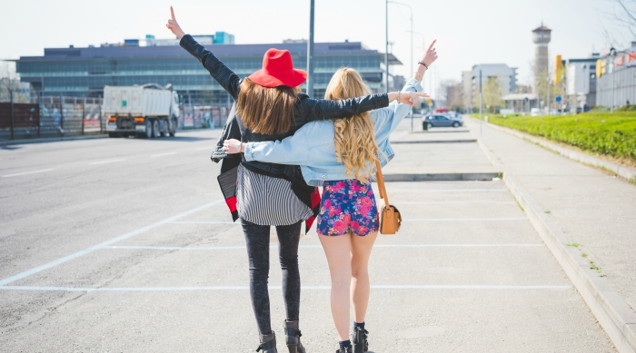 Blonde and brunette girl walking with their arms around each other and arms in the air
