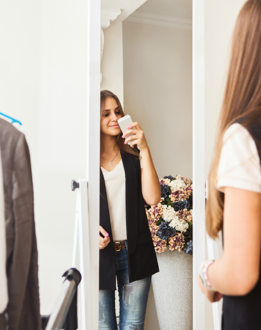 A young woman looking in the mirror at her outfit