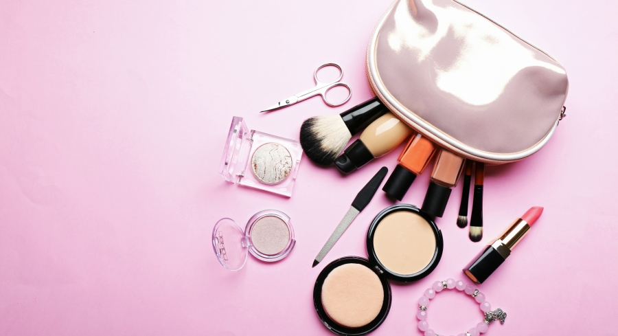 Makeup bag on pink background with its contents spilling out