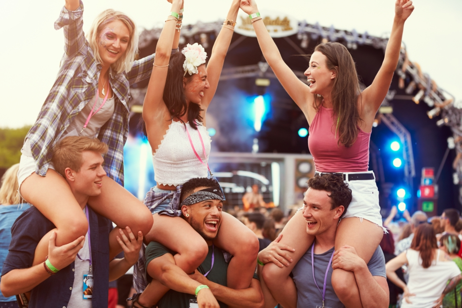 girls on shoulders of boys at music festival