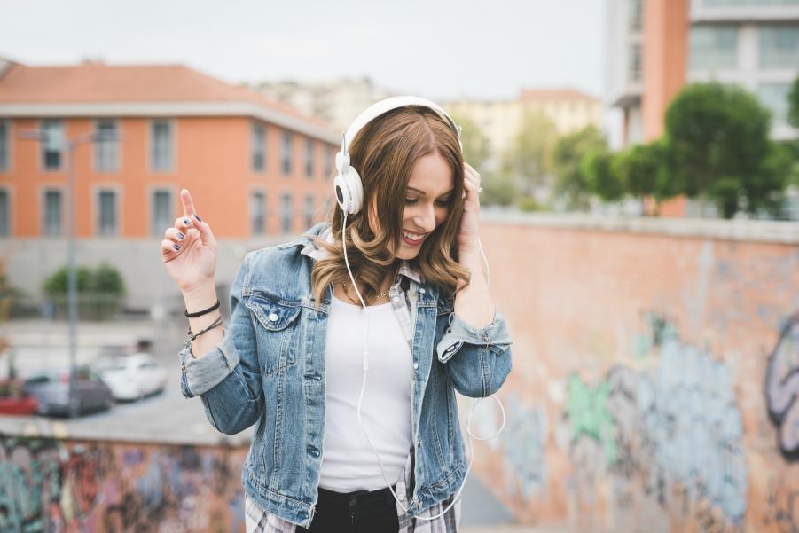 Girl in denim jacket listening to music through white headphones