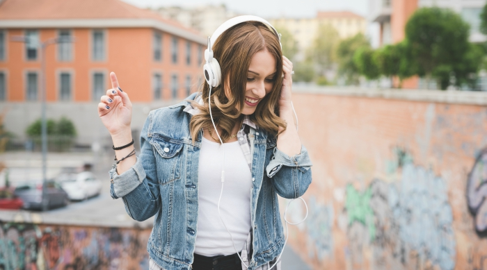Girl in denim jacket listening to music through white headphones