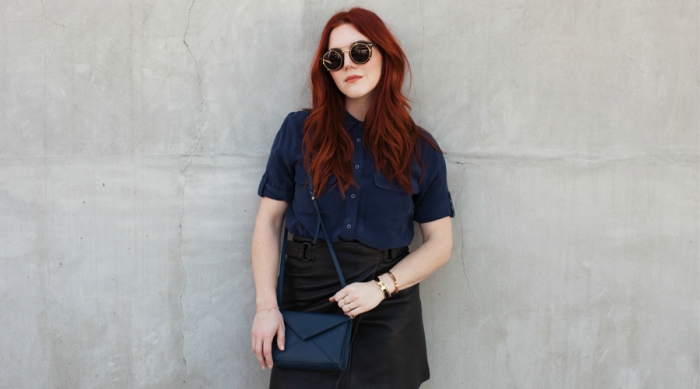 Girl with vibrant red hair wearing a navy blue top and a black leather skirt while leaning on a cement wall