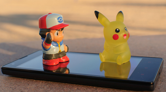 Pokemon figurines sitting on a cell phone