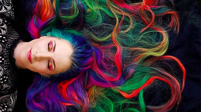 Trisha Reibelt laying down in the grass with her rainbow hair