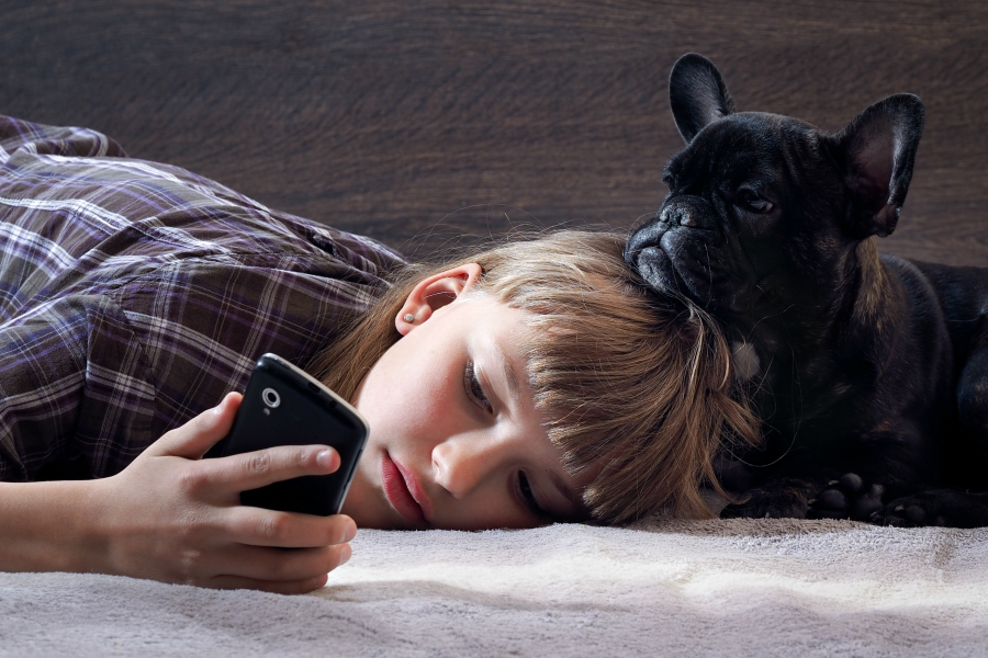 Sad girl laying on her side checking phone with pet dog .