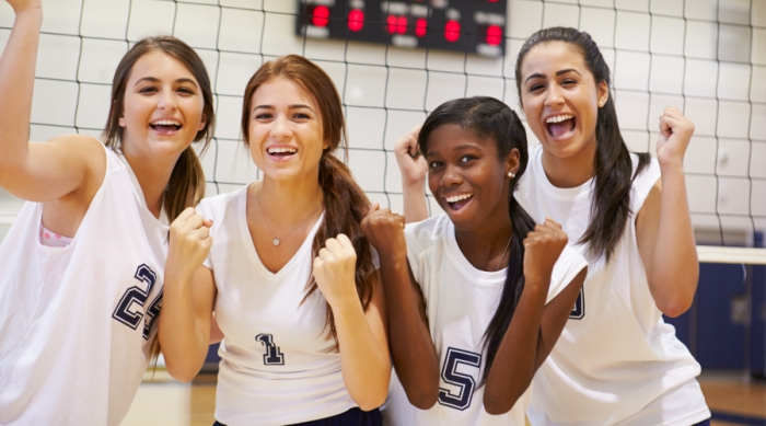 Group of girls cheering in front of a volleyball net