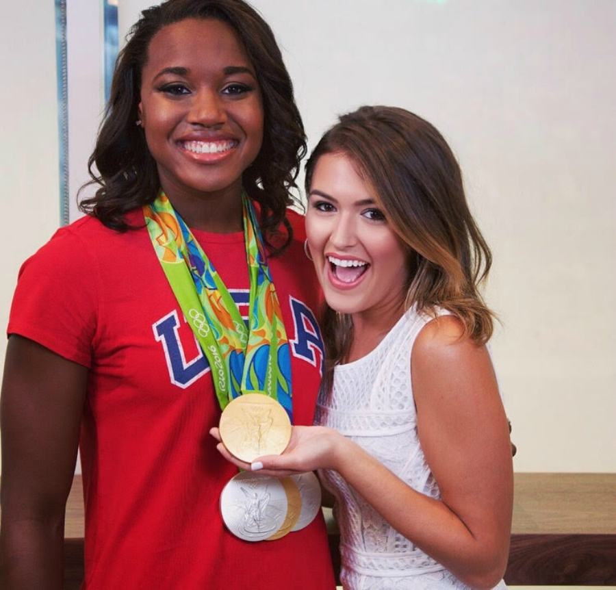 Cassie DiLaura holding Simone Manuel's Gold Medal