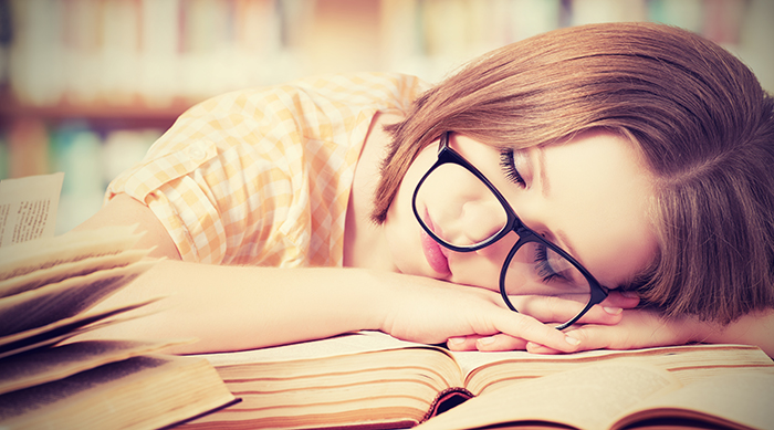 Student with glasses sleeping on her books