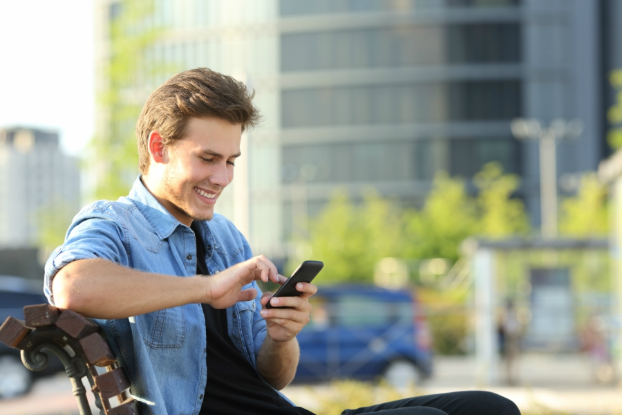 Cute guy smiling while looking at his phone