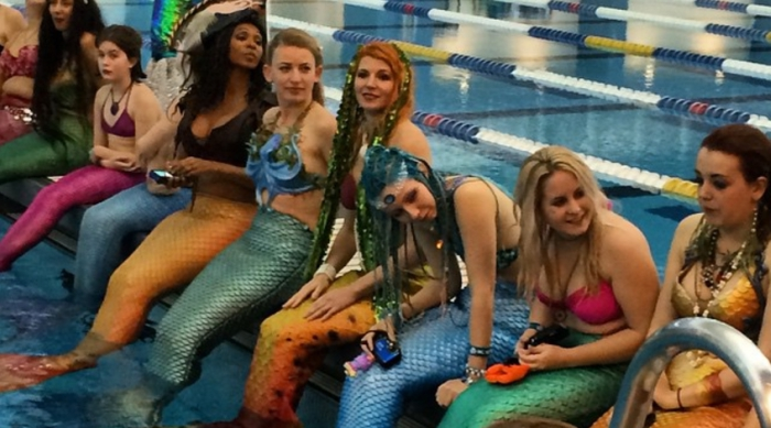 Girls with mermaid tails on sitting in a pool