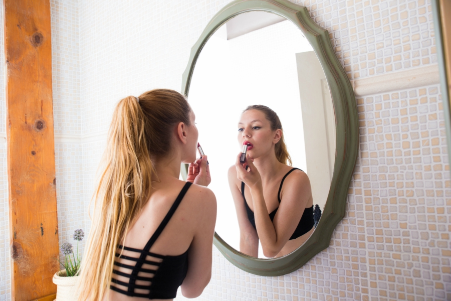 Teen girl putting on lipstick in front of a mirror