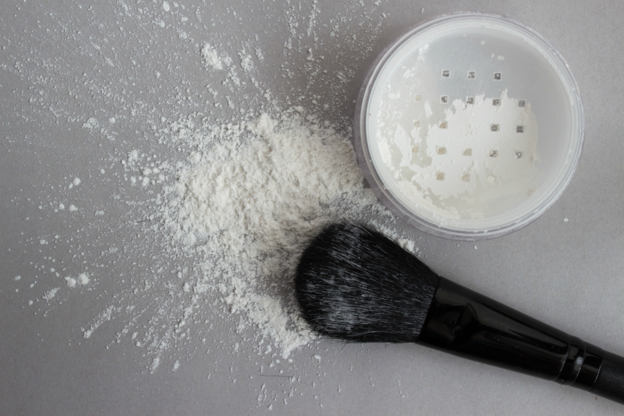 Translucent powder spilled on a gray table with a brush