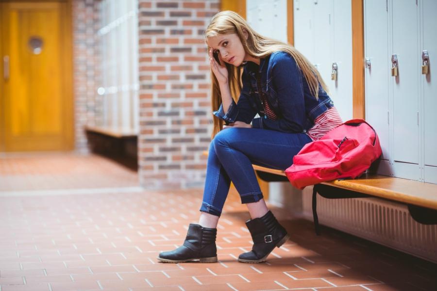 Upset girl sitting in front of school lockers.
