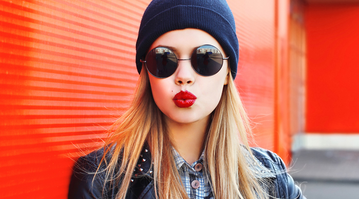 Girl wearing beanie, sunglasses, red lipstick and a leather jacket