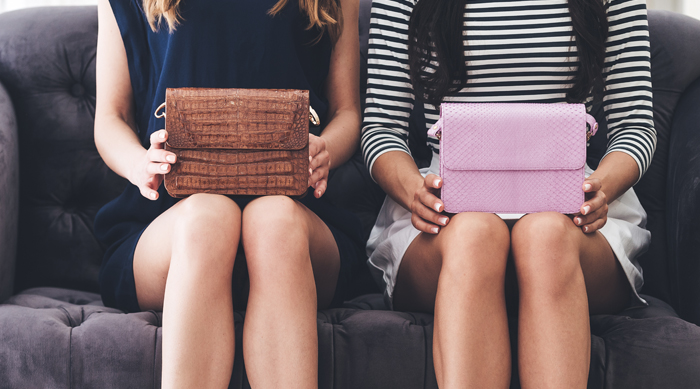 Girls sitting on sofa with purses