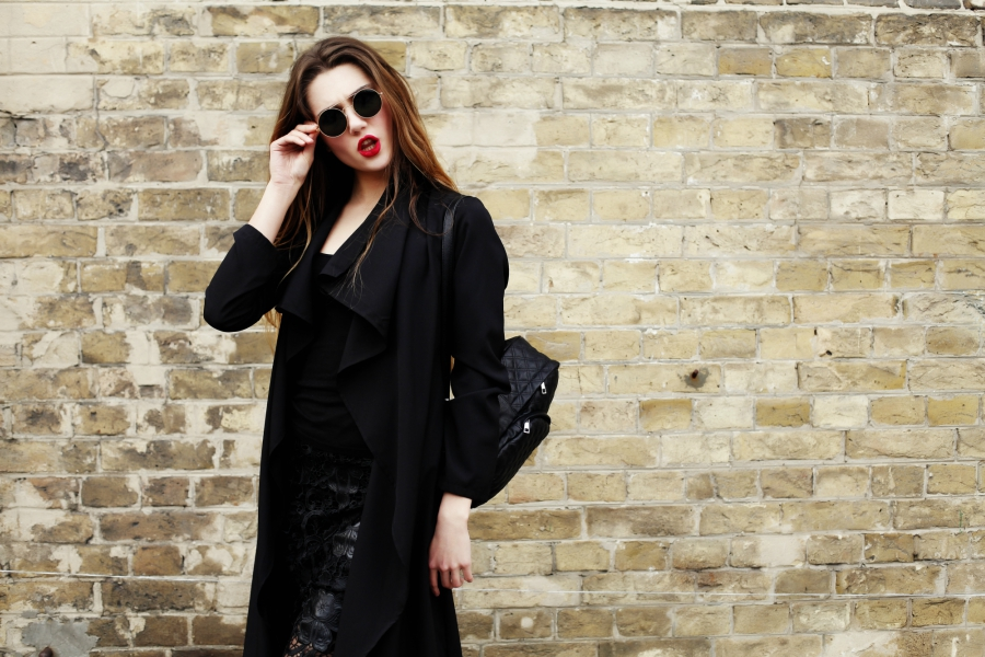 Girl wearing an all-black wardrobe in front of a brick wall