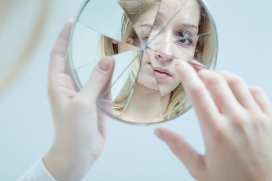 Girl looking into a broken mirror