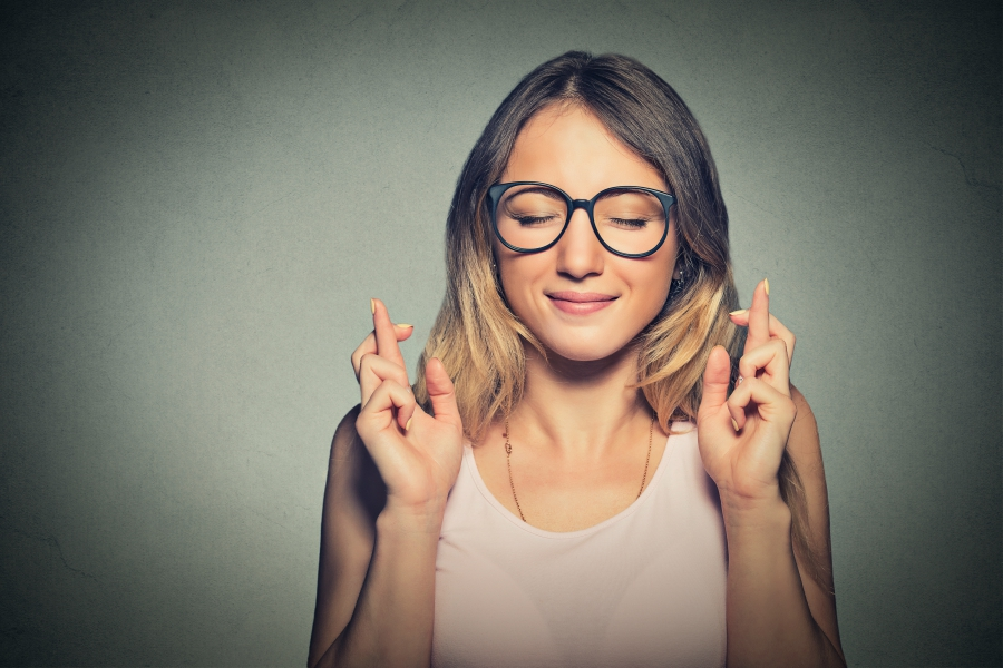 Girl wearing glasses with her eyes closed crossing both sets of fingers on each of her hands