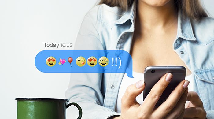 Girl sending emojis on her smart phone