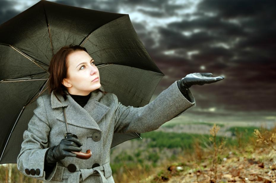 girl with umbrella stands under gloomy raincloud