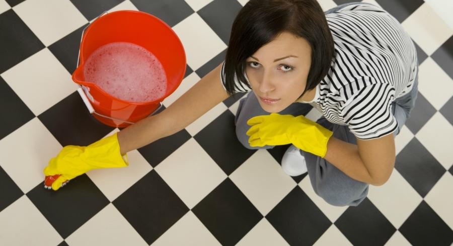 miserable girl scrubs floor at work