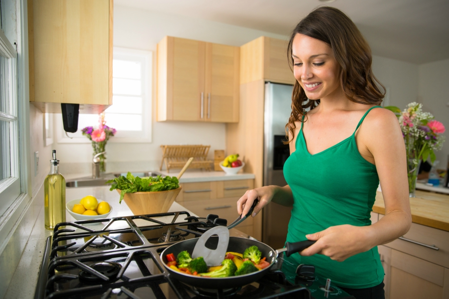 Girl cooking vegetables in a pan in the kitchen