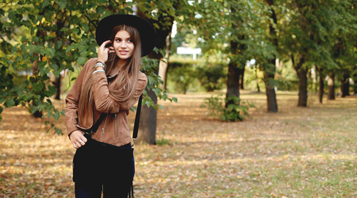 Girl wearing fall fashion and tucking her hair behind her ear