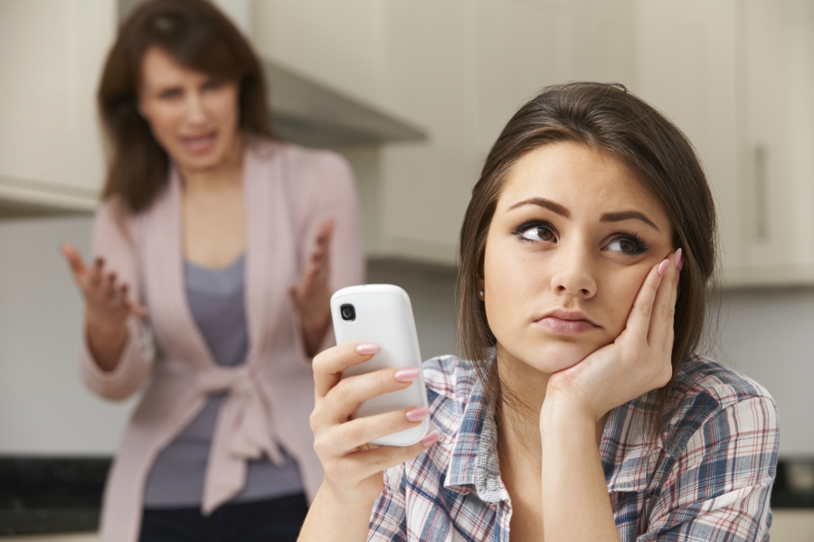 A girl annoyed with her mother and staring at her cell phone