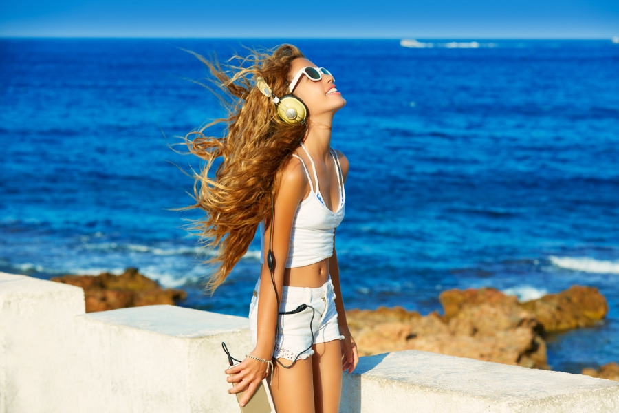 Girl in a white tank top and bleached denim shorts listening to music through her headphones while at the beach