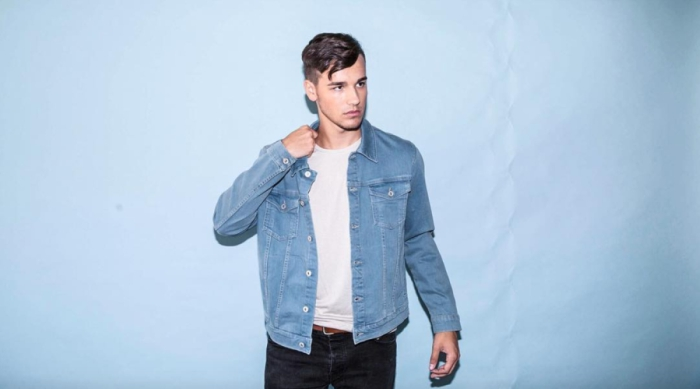Jacob Whitesides standing in front of a blue wall
