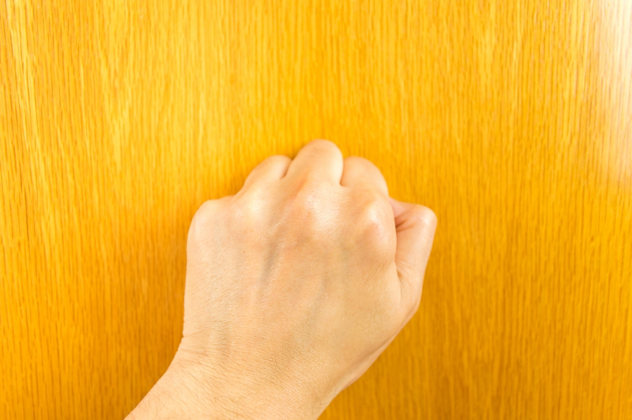Person with a closed fist knocking on wood