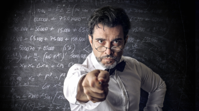 Mean teacher standing in front of chalkboard with math equations.