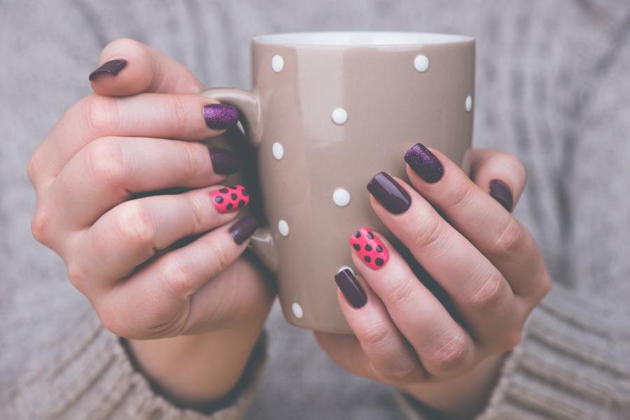 Girl with nail art holding a polka dot mug