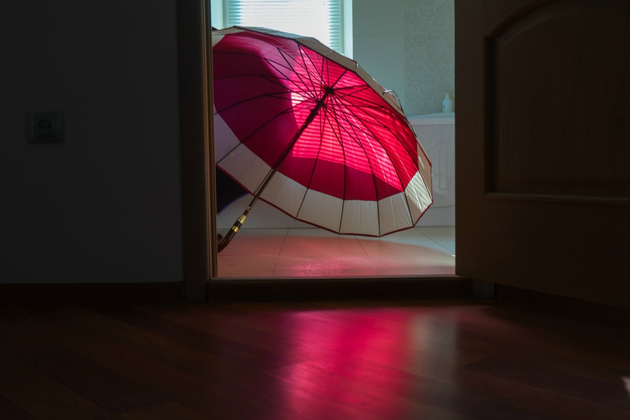 Pink umbrella open on the bathroom floor