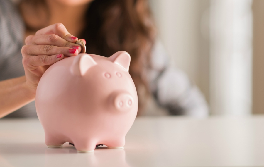 Young girl putting money in a piggy bank
