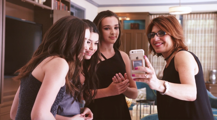 Group of girls looking at photo on iPhone