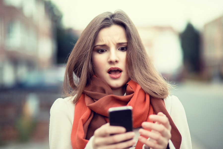 Girl looking at her phone in horror