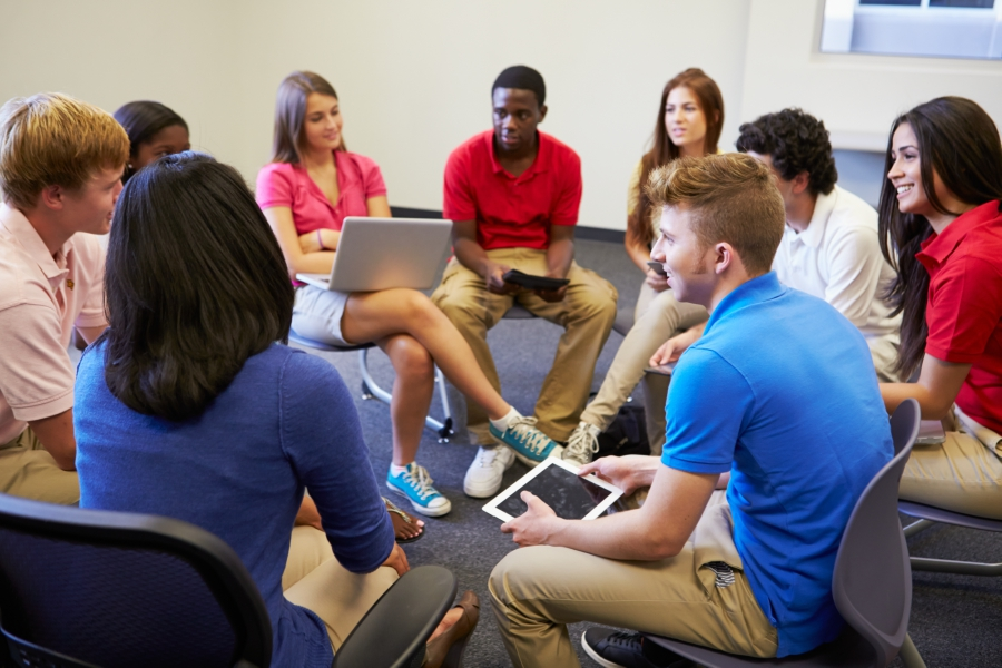 Students sitting in a circle debating and having a discussion