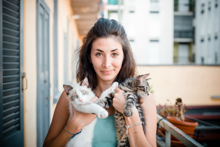 Brown haired woman holding tow kittens in her arms