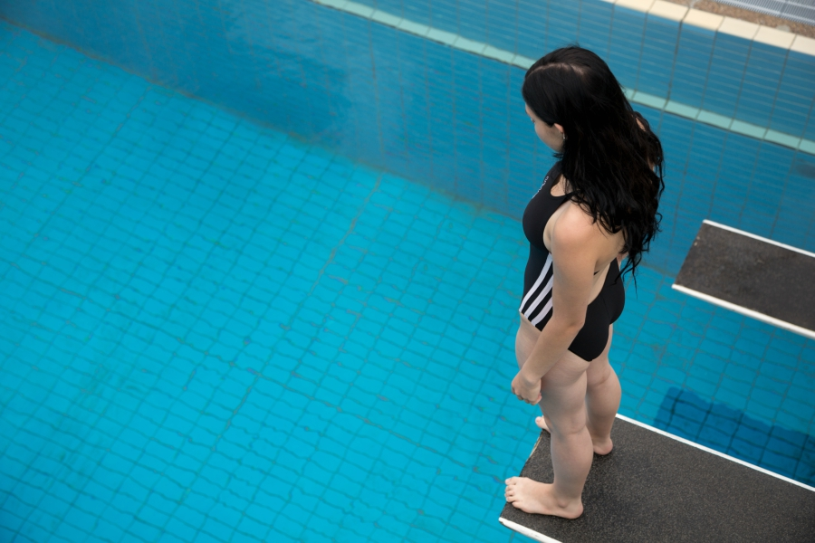 Girl standing on diving board looking down at water