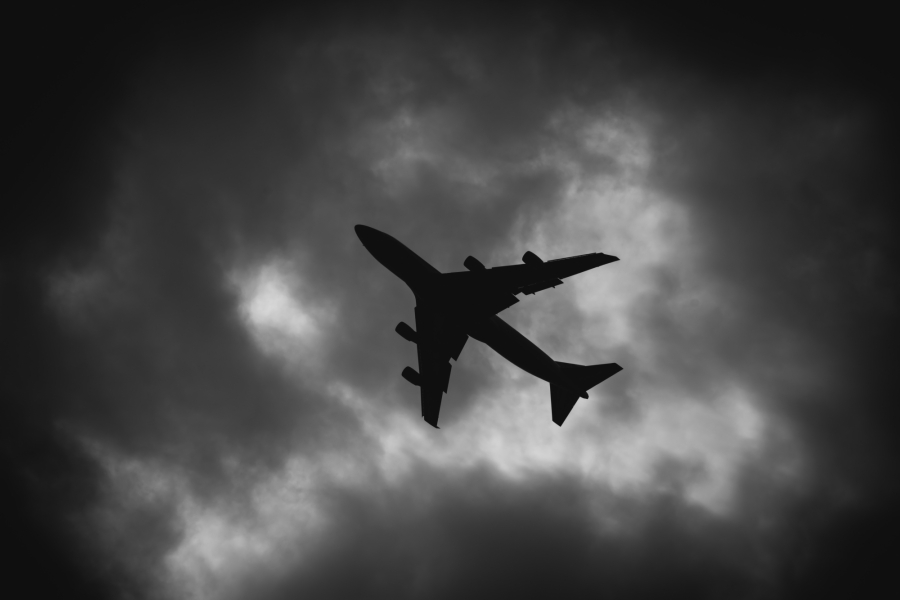 Plane flying over an ominous black and white sky