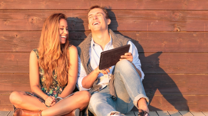 Guy and girl sitting on dock laughing at something on iPad