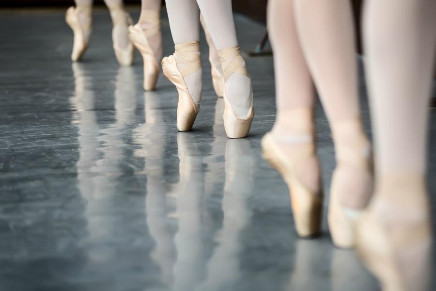 Row of ballerinas on pointe in ballet class.