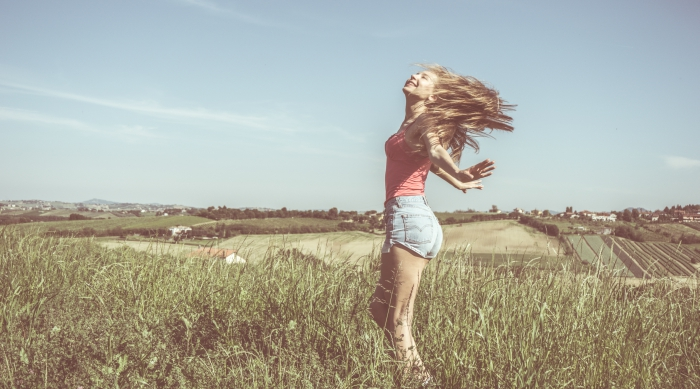 Girl twirling in a field wearing shorts and a tank top