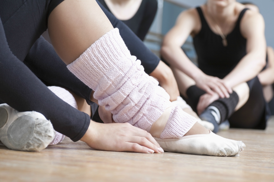 Group of dancers waiting on floor for class to begin. Close up of leg warmers.