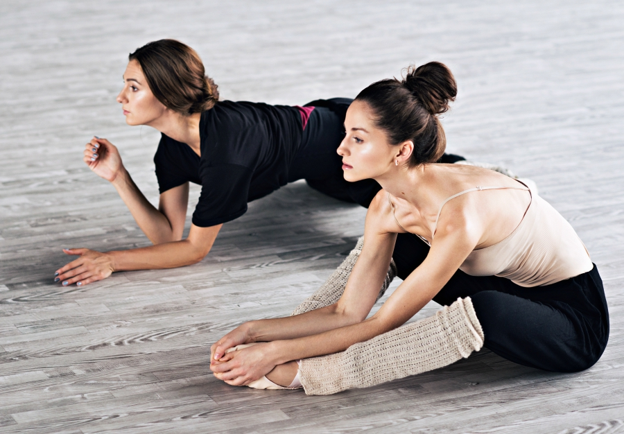 Two dancers stretching on the floor.