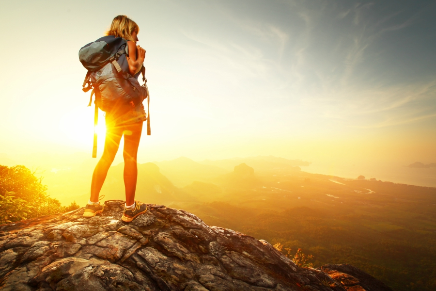 Girl on an early morning hike watching the sunrise from a mountain.