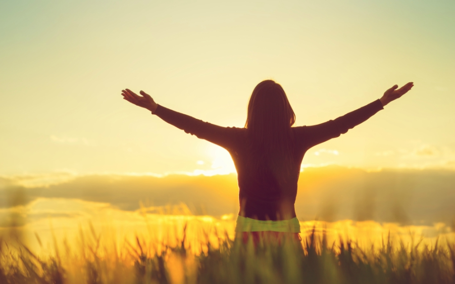 Girl standing in field while sun is setting with her arms stretched wide open